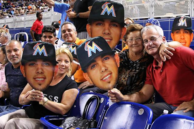 Jose Fernandez's family holds up signs with his face during a game against the Atlanta Braves at Marlins Park on Sept. 25, 2015, in Miami. (Getty Images)
