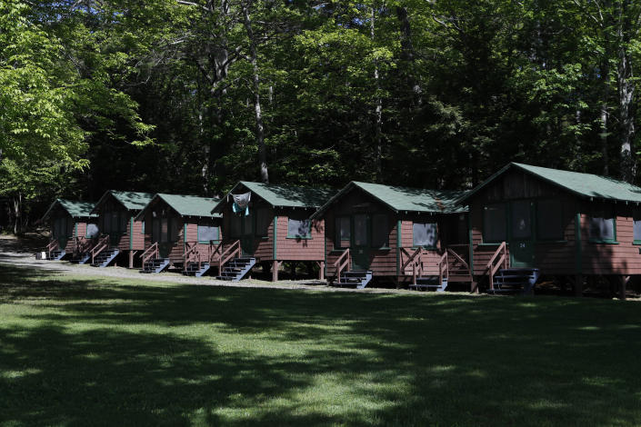 In this Thursday, June 4, 2020 photo, a row of cabins will soon be occupied by campers at the Camp Winnebago summer camp in Fayette, Maine. The boys camp is going ahead with plans to open with a reduction in the number of campers and other changes to comply with guidelines for helping prevent the spread of the coronavirus. Many of the nation's 15,000-plus summer camps opting to close because of health concerns surrounding the pandemic, or because of delays in receiving rules or guidelines from licensing officials. (AP Photo/Robert F. Bukaty)