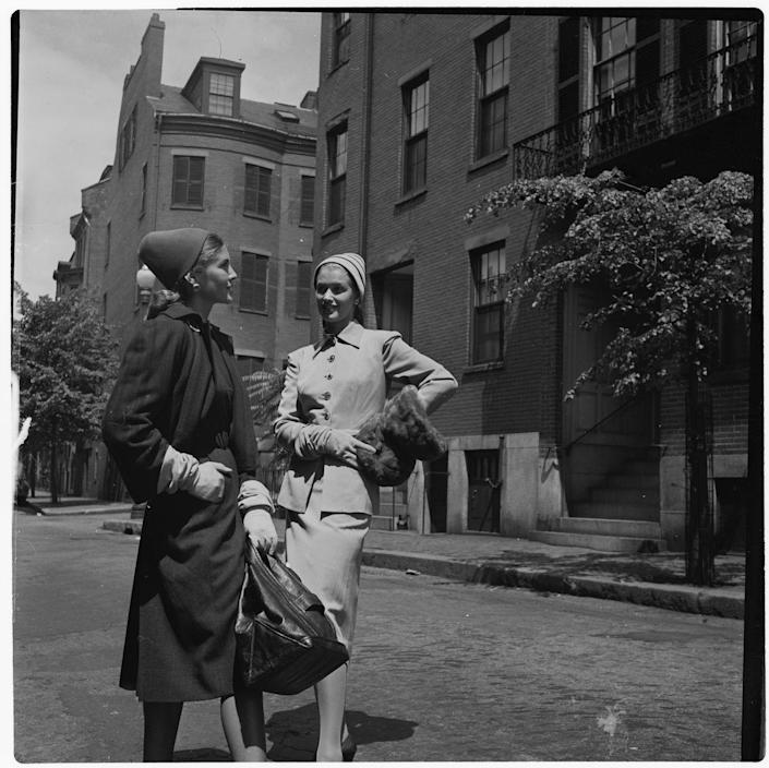 <p>A woman models a herringbone tweed suit (left) by Claire McCardell, while another model shows off a Juilliard gabardine wool suit by Eisenberg in Boston's Louisburg Square.<br></p>