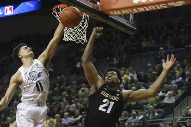 Oregon's Will Richardson, left, and Colorado's Evan Battey, center, go up for a rebound during the second half of an NCAA college basketball game in Eugene, Ore., Thursday, Feb. 13, 2020. (AP Photo/Chris Pietsch)