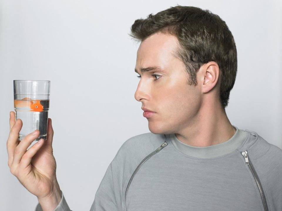 Man looking at goldfish in a glass about to drink it