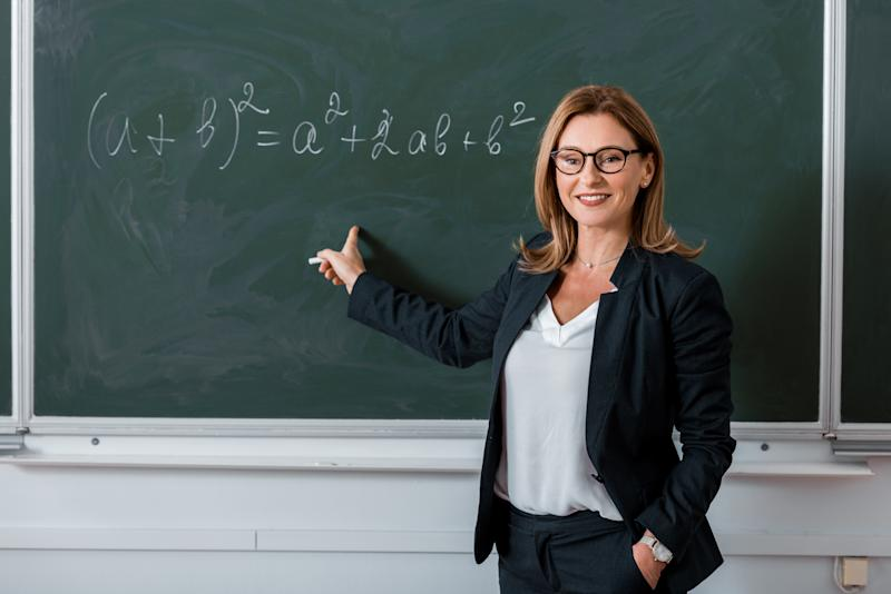 female teacher pointing with finger at mathematical equation on chalkboard in class