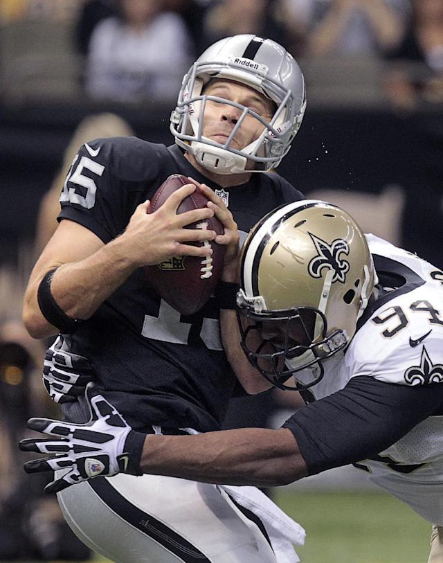 Oakland Raiders quarterback Matt Flynn (15) is sacked by New Orleans Saints defensive end Cameron Jordan (94) in the first half of an NFL preseason football game at the Mercedes-Benz Superdome in New Orleans, Friday, Aug. 16, 2013. (AP Photo/Matthew Hinton)