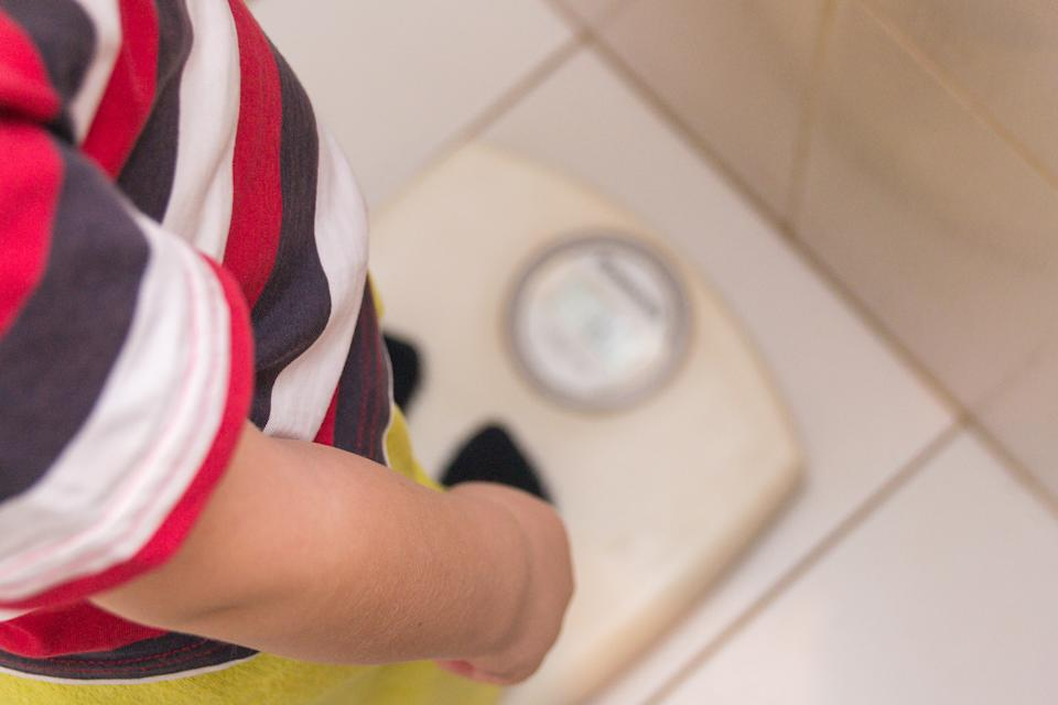 The child stands on the floor scales in a striped T-shirt, the view from the top. Health, objects.