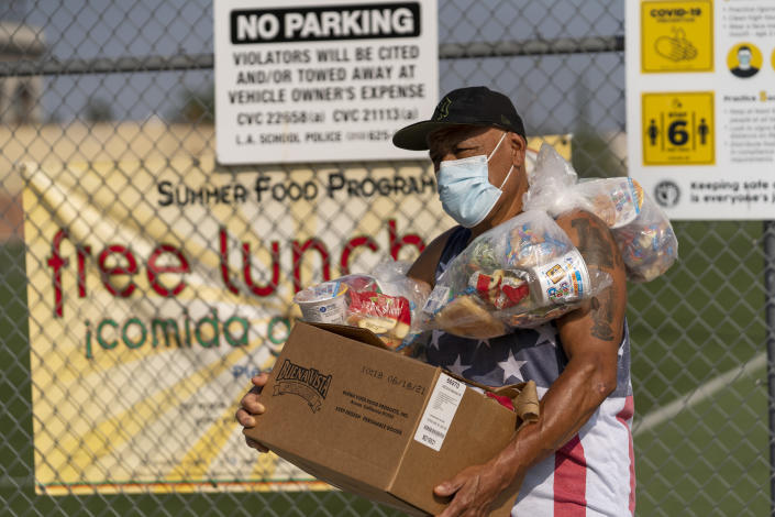 Parent Ernesto Cortes manages to carry his children's free school lunches and a weekend family box, after picking them up on Friday, July 16, 2021, at the Los Angeles Unified School District's Liechty Middle School in Los Angeles. Flush with cash from an unexpected budget surplus, California is launching the nation's largest statewide universal free lunch program. When classrooms open for the fall term, every one of California's 6.2 million public school students will have the option to eat school meals for free, regardless of their family's income. (AP Photo/Damian Dovarganes)