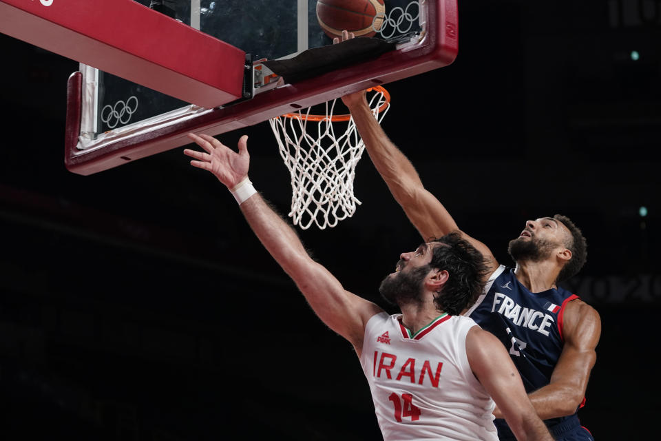 Iran's Mohammadsamad Nik Khahbahrami (14), left, is fouled by France's Rudy Gobert (27) during men's basketball preliminary round game at the 2020 Summer Olympics, Saturday, July 31, 2021, in Saitama, Japan. (AP Photo/Charlie Neibergall)