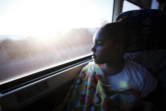 "Erika, 11, watches the sun rise as she takes an overnight bus from Los Angeles to San Quentin state prison in San Quentin, California June 8, 2012. An annual Father's Day event, ""Get On The Bus"" brings children in California to visit their fathers in prison. Sixty percent of parents in state prison report being held over 100 miles (161 km) from their children. Regular prison visits lower rates of recidivism for the parent, and make the child better emotionally adjusted and less likely to become delinquent, according to The Center for Restorative Justice Works, the non-profit organization that runs the ""Get on the Bus"" program."