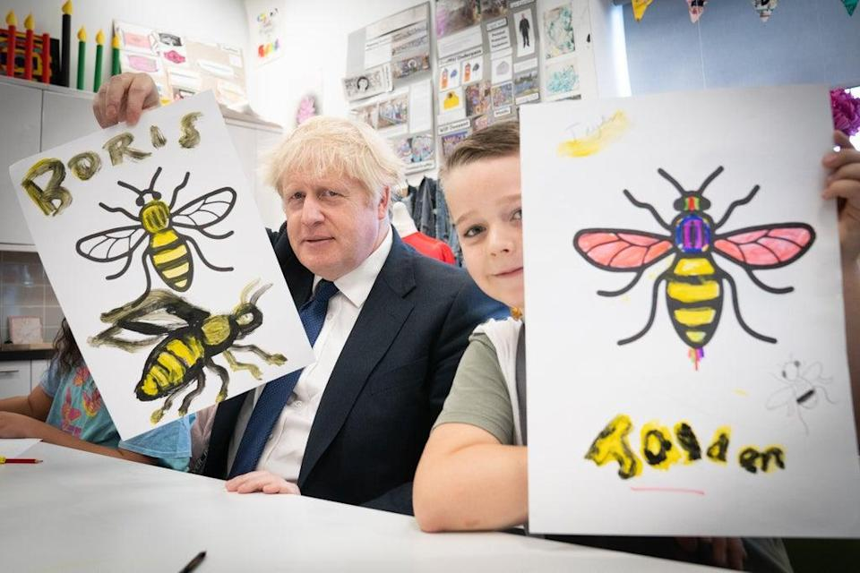 Prime Minister Boris Johnson shows off a picture he painted during a class at HideOut Youth Zone in Manchester (Stefan Rousseau/PA) (PA Wire)
