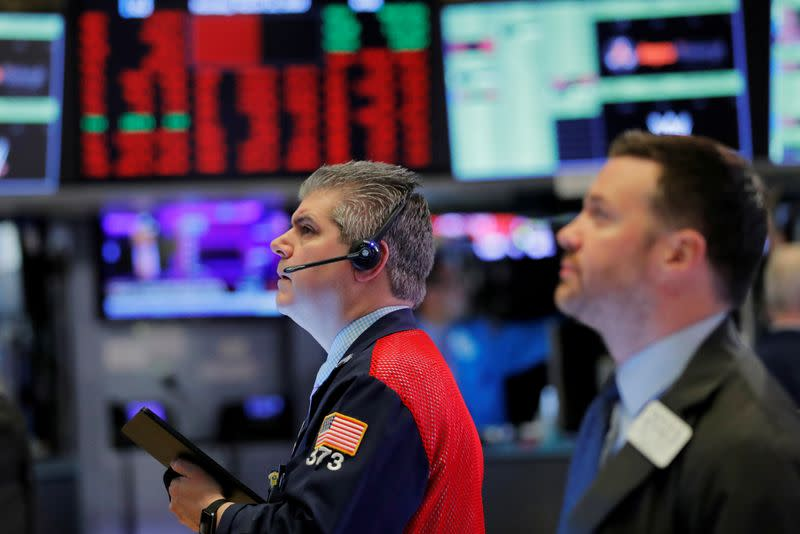 FILE PHOTO: Traders work on the floor of the New York Stock Exchange shortly after the opening bell as trading is halted in New York
