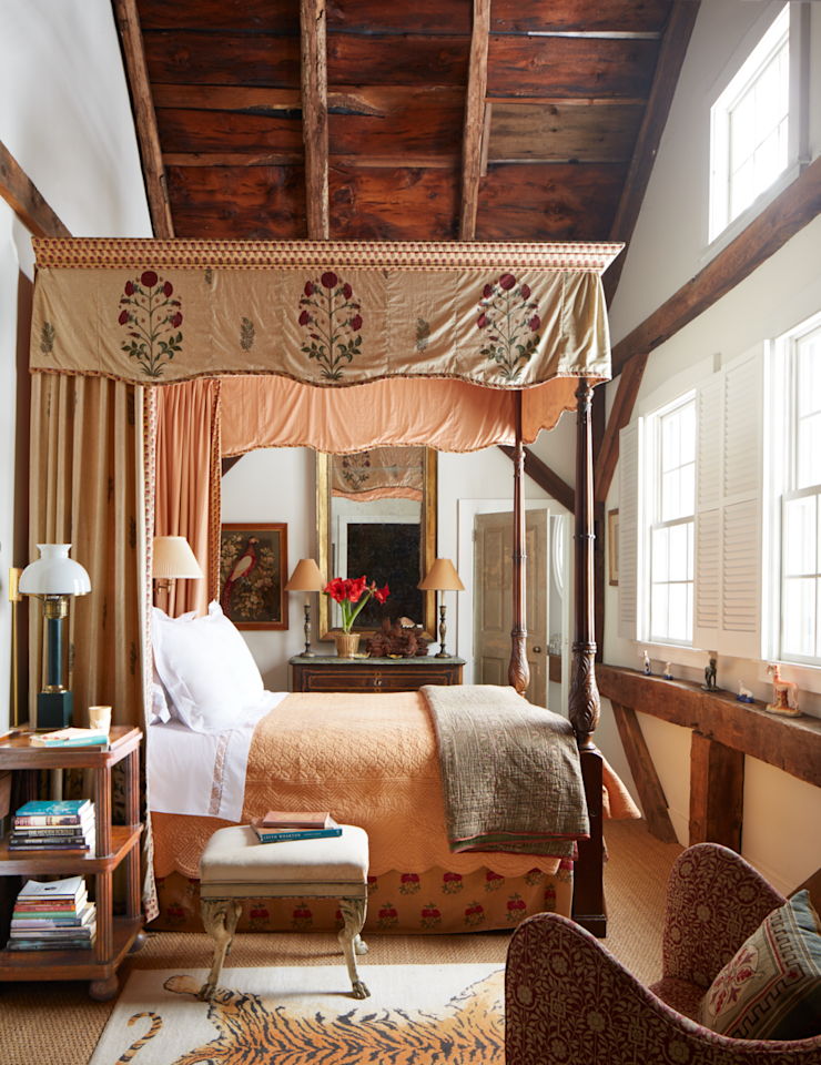 """<p>In a former hayloft of this renovated Connecticut barn, an 18th-century mahogany English bed topped with a canopy of antique Indian textiles complements the natural beige-and-red palette of the <a href=""""https://bunnywilliams.com/"""" target=""""_blank"""">Bunny Williams'</a> and <a href=""""http://www.johnrosselli.com/"""" target=""""_blank"""">John Rosselli's</a> holiday retreat.  The Tibetan silk tiger rug lies on a sea-grass carpet. The English tiered side table and wing chair from <a href=""""http://johnrosselliantiques.com/"""" target=""""_blank"""">John Rosselli Antiques</a> were re-covered in a <a href=""""https://www.robertkime.com/"""" target=""""_blank"""">Robert Kime</a> fabric. </p>"""