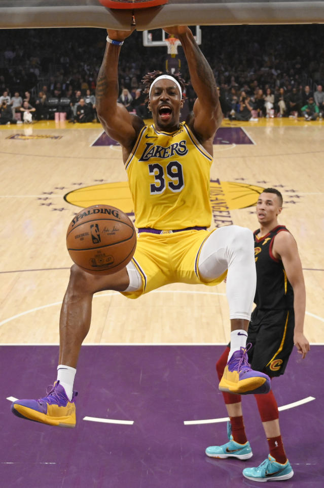 Los Angeles Lakers center Dwight Howard, left, dunks as Cleveland Cavaliers guard Dante Exum watches during the first half of an NBA basketball game Monday, Jan. 13, 2020, in Los Angeles. (AP Photo/Mark J. Terrill)