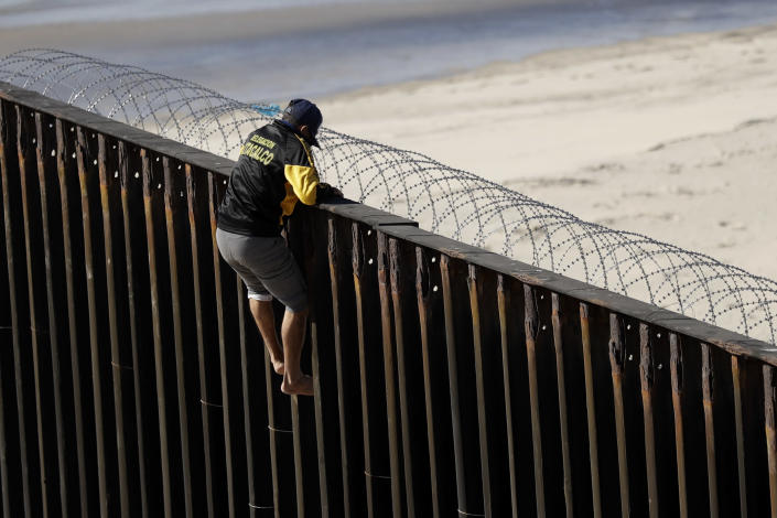 <p>A man tries to get over a border structure topped with concertina wire Wednesday, Nov. 14, 2018, in Tijuana, Mexico. Migrants in a caravan of Central Americans scrambled to reach the U.S. border, catching rides on buses and trucks for hundreds of miles in the last leg of their journey Wednesday as the first sizable groups began arriving in the border city of Tijuana. (Photo: Gregory Bull/AP) </p>