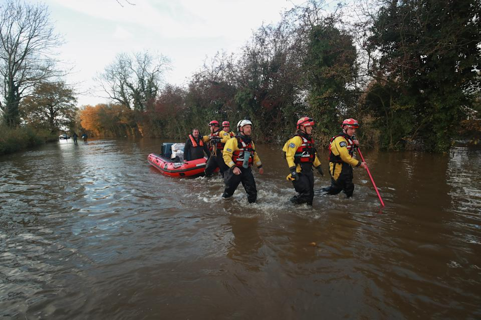 Rescuers pull a boat through floodwater in Fishlake, Doncaster. The Prime Minister is set to chair a meeting of the Government's emergency committee after severe flooding in parts of the country, where rain is finally expected to ease this afternoon.
