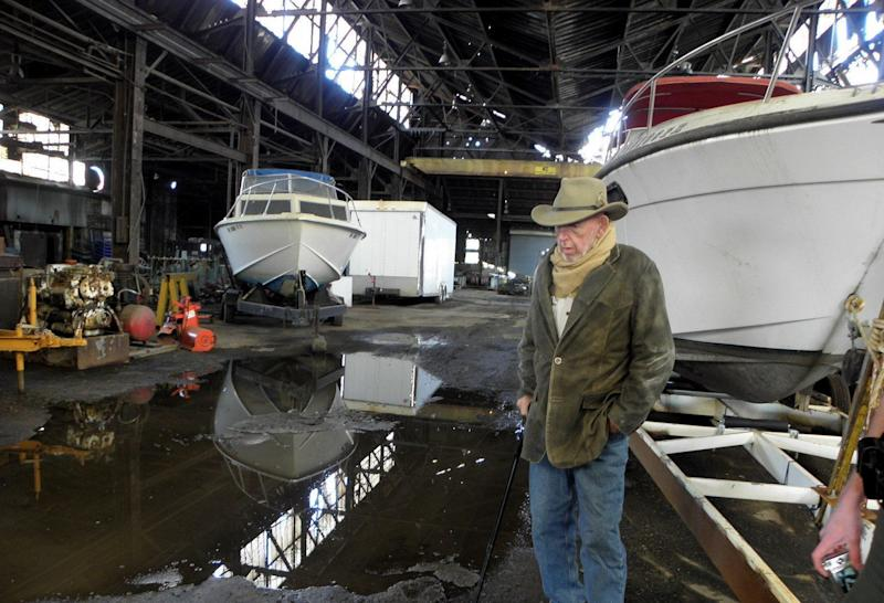 """R.C. """"Heck"""" Heckert inspects fire and water damage at one of his buildings adjacent to the site of the IEI fire. Heckert, who runs a taxi service and operates riverboats, says he lost three buildings to the fire, but doesn't blame IEI owners."""