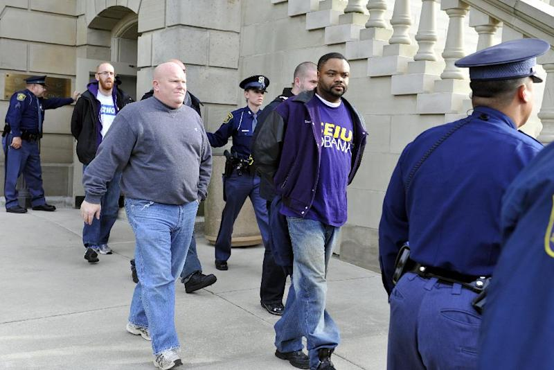 Protesters are led out of the State Capitol Building in handcuffs after demonstrating against right-to-work legislation inside the Capitol in downtown Lansing, Mich. Thursday, Dec. 6, 2012. Eight people were arrested for resisting and obstructing when they tried to push past two troopers guarding the Senate door, state police Inspector Gene Adamczyk said. The Capitol was temporarily closed because of safety concerns. (AP Photo/The State Journal, Rod Sanford)