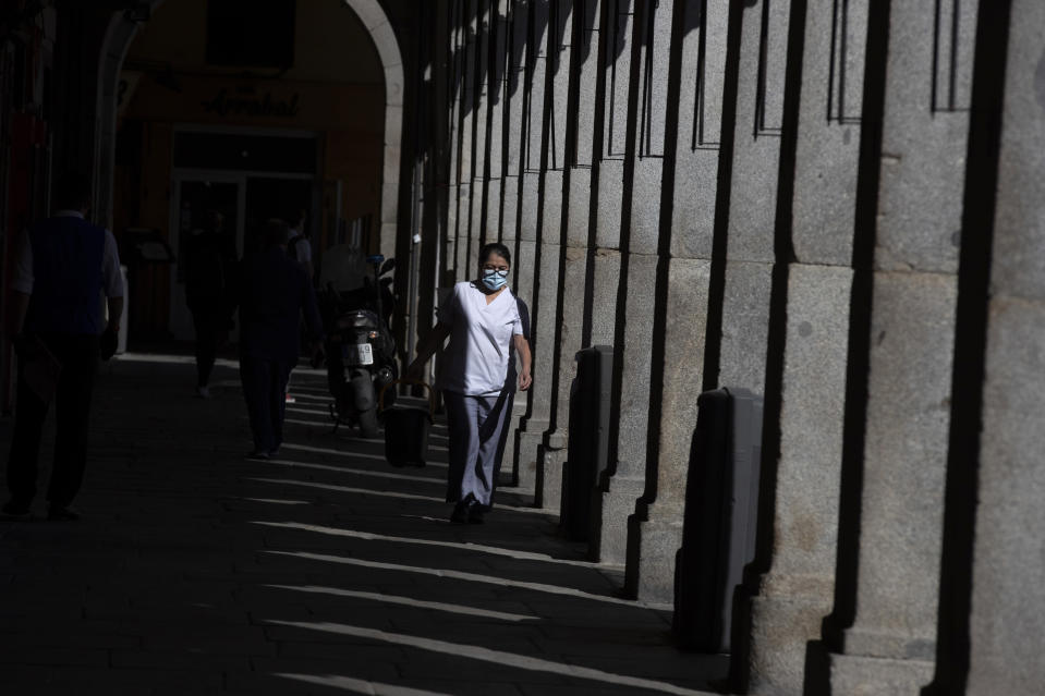 A cleaner wearing a face mask to prevent the spread of coronavirus works at the Plaza Mayor square in downtown Madrid, Spain, Friday, Oct. 9, 2020. Spanish Prime Minister Pedro Sánchez is holding a Cabinet meeting to consider declaring a state of emergency for Madrid in order to impose stronger anti-virus restrictions on reluctant regional authorities. (AP Photo/Manu Fernandez)