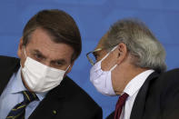 Brazil's President Jair Bolsonaro and Economy Minister Paulo Guedes wear protective face masks during a ceremony announcing economic measures to support philanthropic hospitals and help them treat COVID-19 patients, at the Planalto Presidential Palace, in Brasilia, Brazil, Thursday, March 25, 2021. (AP Photo/Eraldo Peres)
