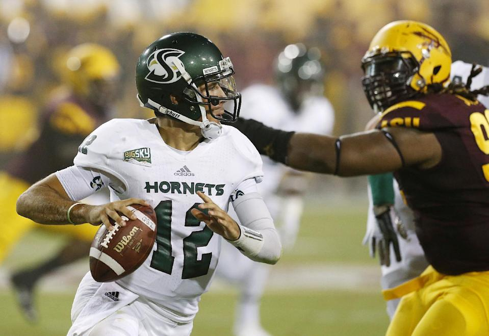 Sacramento State's Garrett Safron (12) scrambles away from Arizona State's Will Sutton during the first half in an NCAA college football game on Thursday, Sept. 5, 2013, in Tempe, Ariz. (AP Photo/Ross D. Franklin)