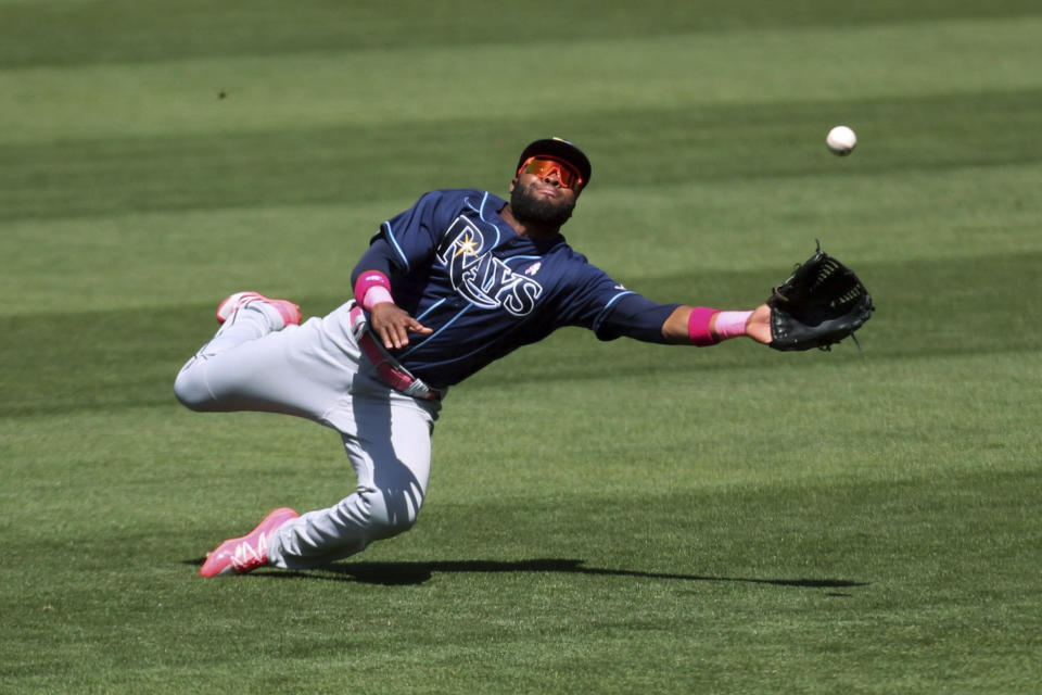 Tampa Bay Rays' Manuel Margot dives for a triple hit by Oakland Athletics' Elvis Andrus during the seventh inning of a baseball game in Oakland, Calif., Sunday, May 9, 2021. (AP Photo/Jed Jacobsohn)