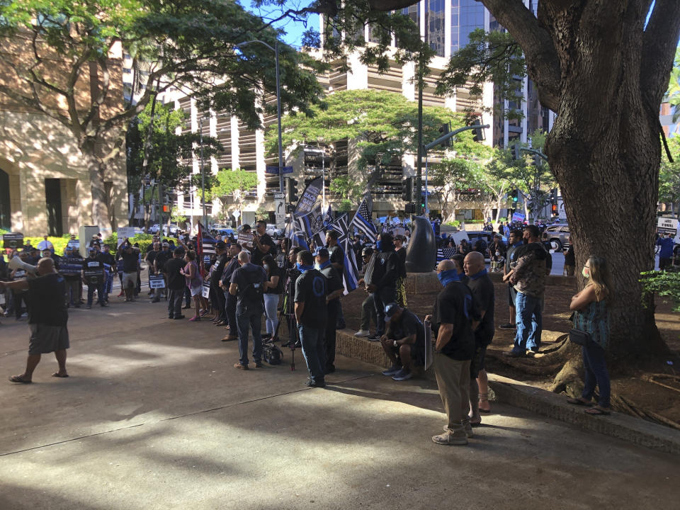 Supporters of three Honolulu police officers charged in connection with the fatal shooting of a 16-year-old gather in front of a downtown Honolulu courthouse on Friday, June 25, 2021. The officers appeared in court to face charges in connection with the fatal shooting of a 16-year-old Micronesian boy, the first cases of their kind against law enforcement in the city in more than 40 years. (AP Photo/Audrey McAvoy)