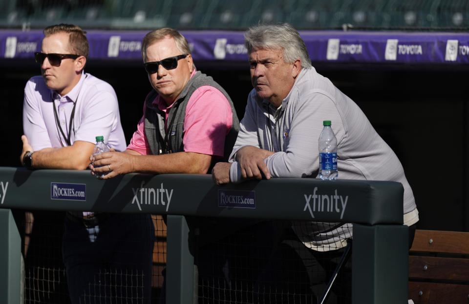 From right, Colorado Rockies interim general manager Bill Schmidt leans over the dugout rail with Marc Gustafson, senior director of scouting operations for the team, and Sterling Monfort, assistant director of scouting operations, as the Rockies warm up before a baseball game against the Los Angeles Dodgers Tuesday, Sept. 21, 2021, in Denver. (AP Photo/David Zalubowski)