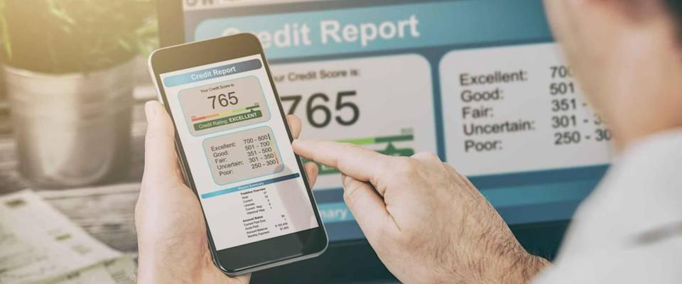 man looking at credit score on phone and laptop screen open behind it