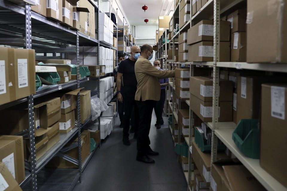 Caretaker Health Minister Hamad Hassan, front, inspects a medical warehouse in Beirut, Lebanon, Friday, June 11, 2021. Hassan raids warehouses in an effort to control those who are hoarding subsidized medical equipment and baby formula in order to sell them later at higher prices or on the black market. (AP Photo/Bilal Hussein)