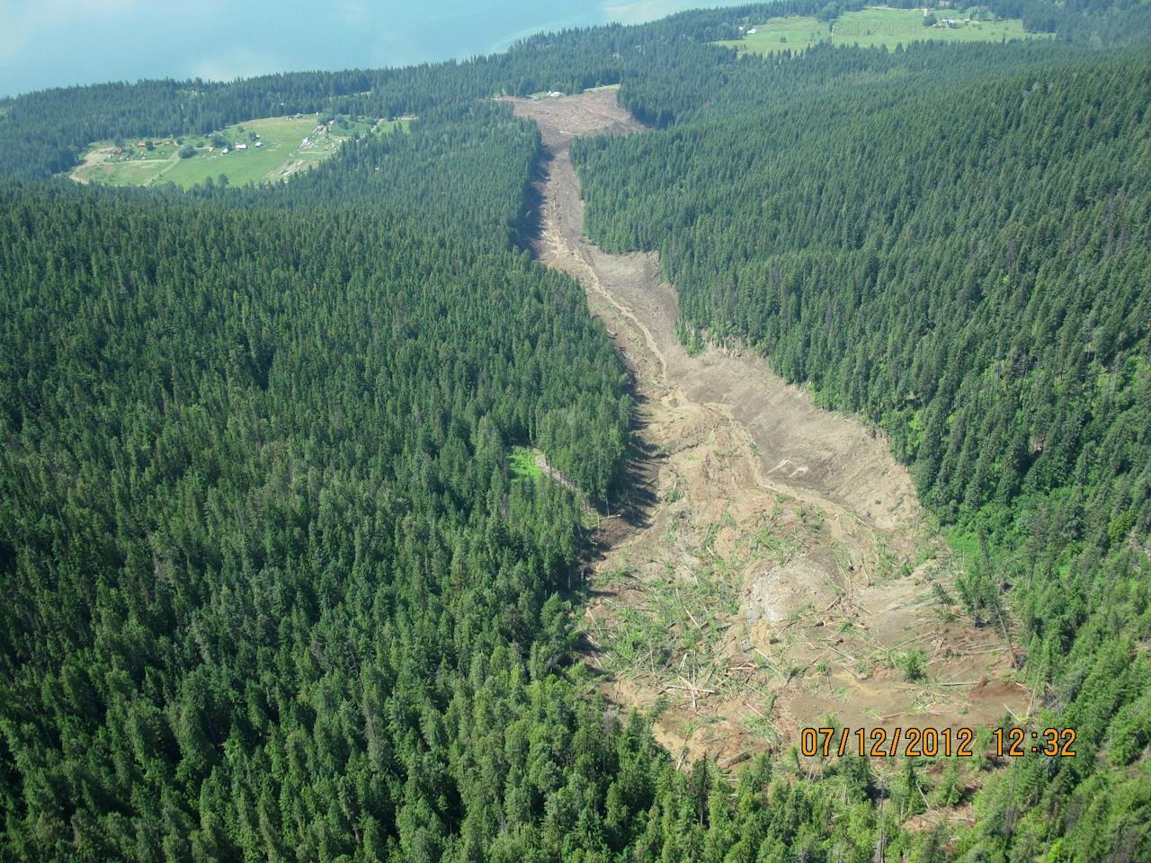 The Johnsons landing landslide is shown in this Thursday July 12, 2012 photo provided by Emergency BC. Four people are still unaccounted for nearly 24 hours after a wall of rock, mud and trees cascaded down the side of a mountain above the shores of Kootenay Lake, tearing through the tiny community of Johnsons Landing, about 70 kilometres northeast of Nelson. At least three homes in the southeastern B.C. hamlet are engulfed by the muck, which is unstable and shifting, prompting searchers to call off rescue efforts at least once on Thursday afternoon. Emergency crews met at dawn Friday to consider the most efficient and effective way to search the massive mudslide for possible victims. (AP Photo/Emergency BC via The Canadian Press) HANDOUT PHOTO; ONE TIME USE ONLY; NO ARCHIVES; NOT FOR RESALE