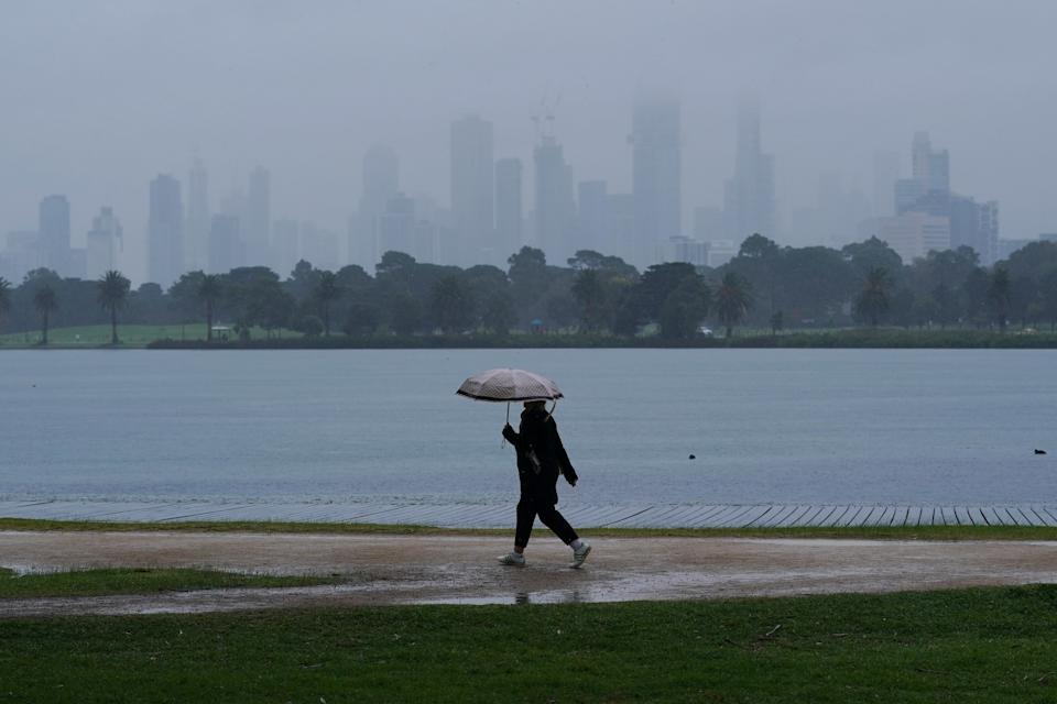 People walk in isolation as heavy rain begins to fall in Melbourne on Wednesday. Source: AAP