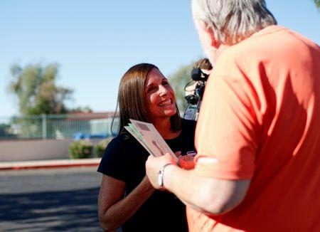 Martha McSally talks to Dennis Williams of Mesa, Arizona as he heads to the polls to vote in the Republican primary for the open U.S. Senate seat, in Mesa, Arizona, U.S. August 28, 2018.  REUTERS/Nicole Neri