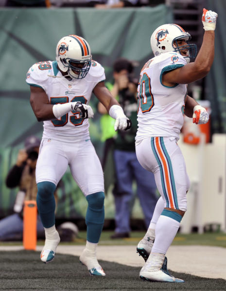 Miami Dolphins' Olivier Vernon (50) celebrates with teammate Jonathan Freeny (59) after returning a blocked punt for a touchdown during the first half of an NFL football game against the New York Jets, Sunday, Oct. 28, 2012, in East Rutherford, N.J. (AP Photo/Bill Kostroun)