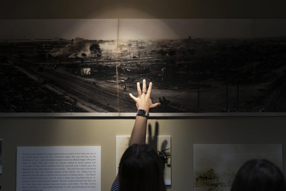 A woman points at a picture of devastation from the Tulsa Race Massacre in a prayer room dedicated to the massacre at the First Baptist Tulsa church during centennial commemorations, Sunday, May 30, 2021, in Tulsa, Okla. The church made the room to provide a place to explore the history of the Tulsa Race Massacre of 1921 and to prayerfully oppose racism. (AP Photo/John Locher)
