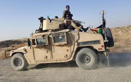 Afghan security forces sit on top of a vehicle as they patrol outside of Kunduz city