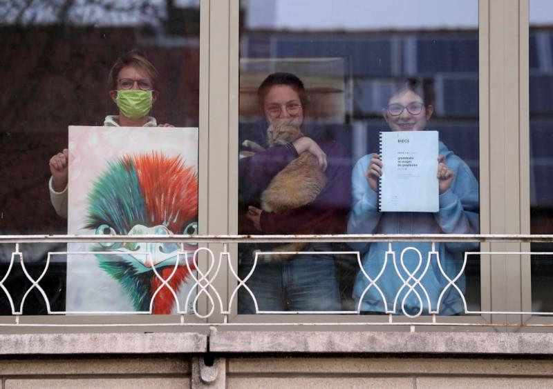 Resident Anne-Sophie Devos and her twin daughters pose behind the window of their home with objects significant to them during the coronavirus lockdown imposed by the Belgian government, in Brussels