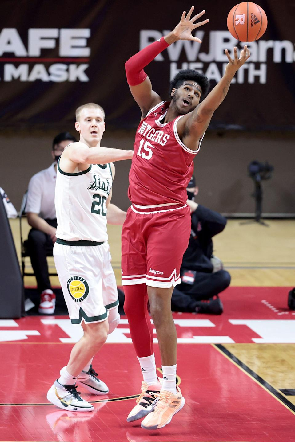 Jan 28, 2021; Piscataway, New Jersey, USA;  Rutgers Scarlet Knights center Myles Johnson (15) jumps for a rebound against Michigan State Spartans forward Joey Hauser (20) during the first half at Rutgers Athletic Center (RAC). Mandatory Credit: Vincent Carchietta-USA TODAY Sports