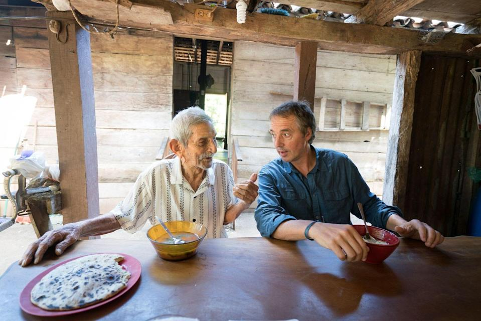Dan Buettner (right) speaking with a centenarian, a person who has reached the age of 100 years.