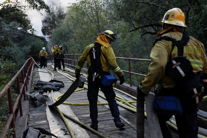 A firefighter works with a hose while working on a burning structure during the Kincade fire in Calistoga, California