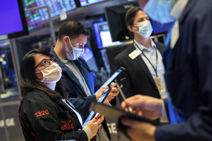 In this photo provided by the New York Stock Exchange, Phyllis Arena Woods, left, works with other traders on the floor, Friday, Feb 26, 2021. Stocks wobbled between small gains and losses on Wall Street Friday as rising technology stocks offset a slide in banks and energy companies. (Courtney Crow/New York Stock Exchange via AP)