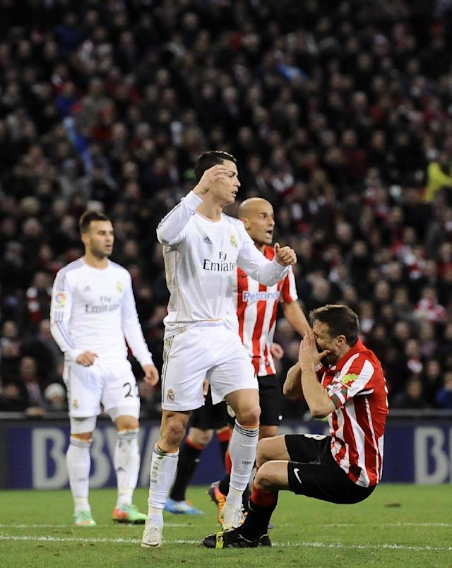 Real Madrid's Cristiano Ronaldo of Portugal, center, gestures after a foul against Athletic Bilbao's Carlos Gurpegi, right, during their Spanish League soccer match against Athletic Bilbao, at San Mames stadium in Bilbao, Spain, Sunday, Feb. 2, 2014. (AP Photo/Alvaro Barrientos)