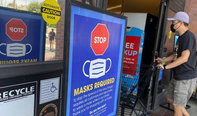 People shop at a grocery store enforcing the wearing of masks in Los Angeles on July 23. (Photo: CHRIS DELMAS via Getty Images)
