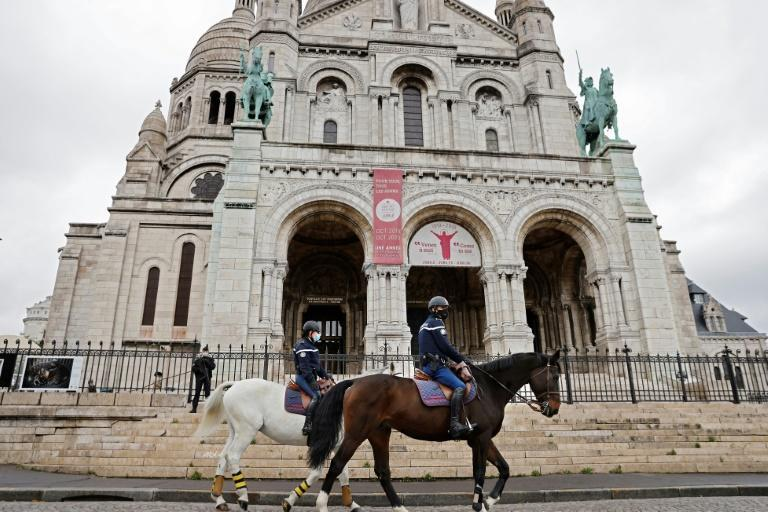 French mounted police patrol in front of the Sacre-Coeur basilica during an All Saints' Day mass in Paris.