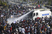 A police truck sprays water to a crowd of protesters in Naypyitaw, Myanmar, Monday, Feb. 8, 2021. In the month since Feb. 1 coup, the mass protests occurring each day are a sharp reminder of the long and bloody struggle for democracy in a country where the military ruled directly for more than five decades. (AP Photo)