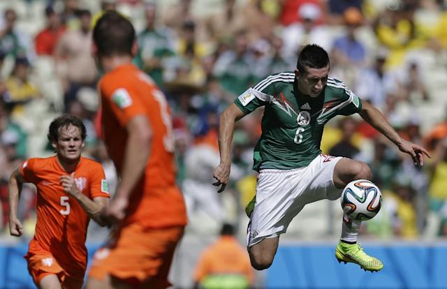 Mexico's Hector Herrera, right, controls the ball during the World Cup round of 16 soccer match between the Netherlands and Mexico at the Arena Castelao in Fortaleza, Brazil, Sunday, June 29, 2014. (AP Photo/Natacha Pisarenko)