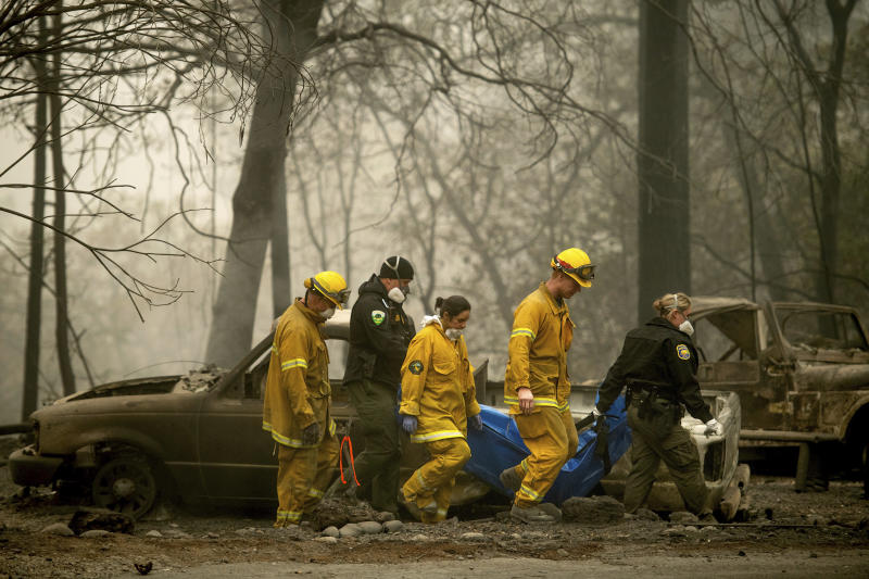 Firefighters recover the body of a Camp fire victim at the Holly Hills Mobile Estates on Wednesday in Paradise, California. Thousands of homes were destroyed when flames hit Paradise, a former gold-mining camp popular with retirees.  (AP Photo/Noah Berge)