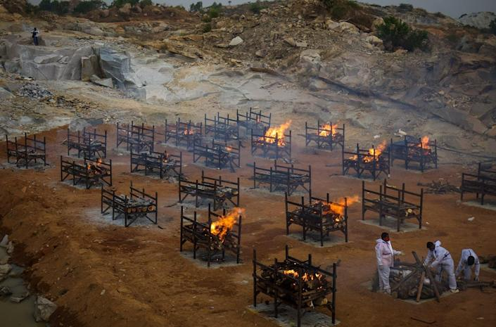 """<span class=""""caption"""">Mass cremations in the city of Bengaluru, India, due to the large number of COVID-19 deaths.</span> <span class=""""attribution""""><a class=""""link rapid-noclick-resp"""" href=""""https://www.gettyimages.com/detail/news-photo/men-wearing-ppe-perform-the-last-rites-of-a-deceased-news-photo/1315456370?adppopup=true"""" rel=""""nofollow noopener"""" target=""""_blank"""" data-ylk=""""slk:Abhishek Chinnappa/Getty Images)"""">Abhishek Chinnappa/Getty Images)</a></span>"""