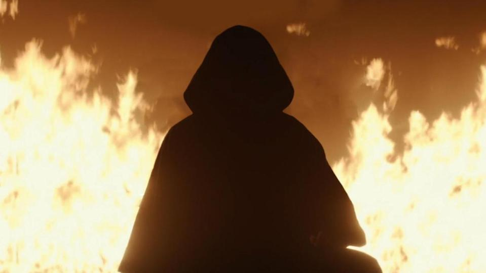 A hooded figure stands in front of flames in Loki