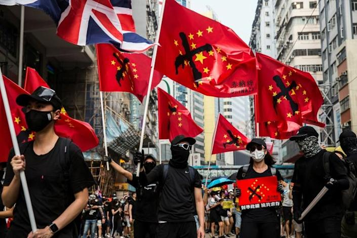 """Many marchers were holding so-called """"Chinazi flags"""", a version of the Chinese flag where the yellow stars are in the shape of a swastika (AFP Photo/ISAAC LAWRENCE)"""