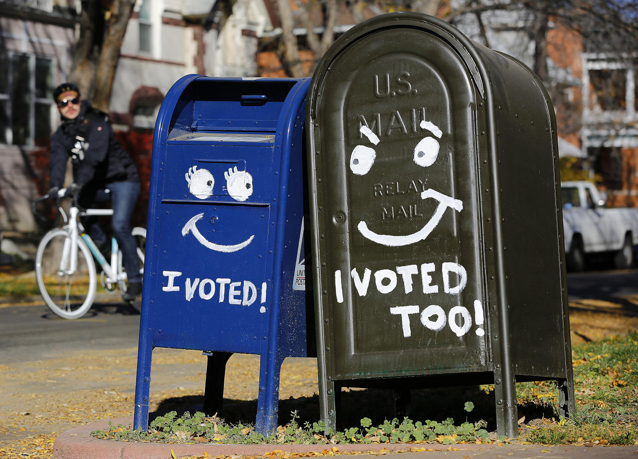 A biker passes by a pair of mailboxes in the Capitol Hill neighborhood November 6, 2012 in Denver, Colorado. Colorado is considered by most experts to be one of the key battleground state in this year's presidential election. (Photo by Marc Piscotty/Getty Images)
