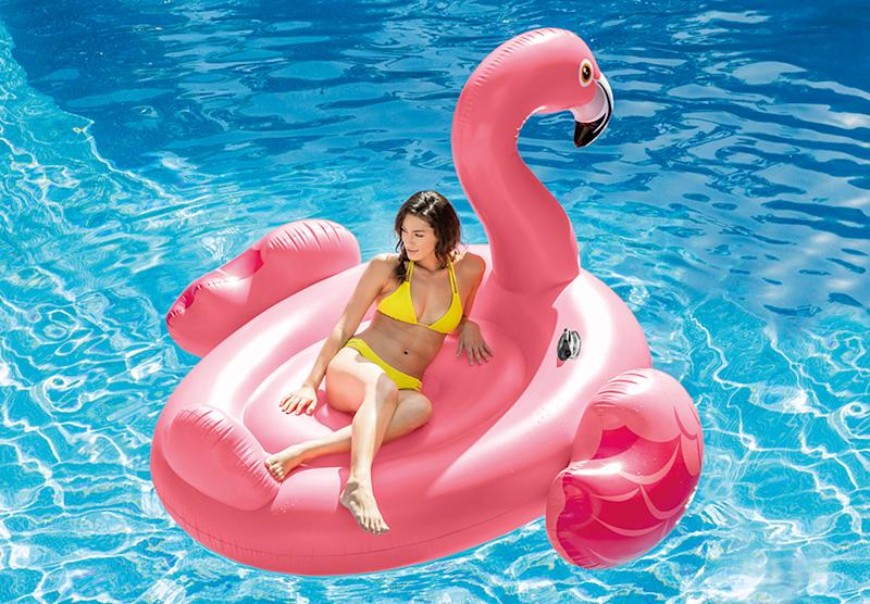 Woman on large pink flamingo pool float in pool