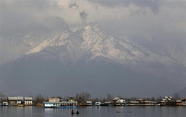 People travel in a small boat on the waters of Dal Lake on a sunny day in Srinagar February 23, 2012.